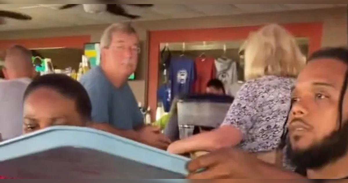 White Man Stares At Black Family Enjoying Their Meal